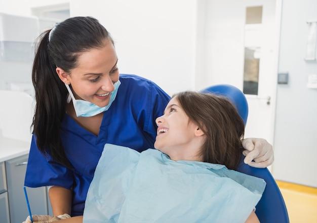 Netter pädiatrischer zahnarzt mit einem lächelnden jungen patienten