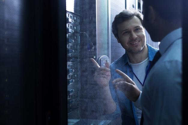 Netter positiv entzückter mann, der lächelt und seinen kollegen ansieht, während er auf usb-kabel zeigt