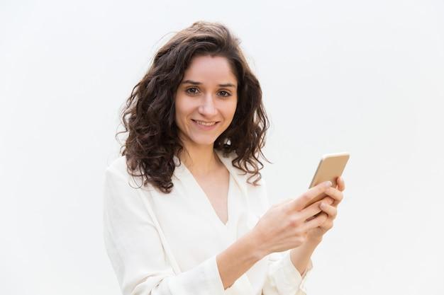 Netter positiver weiblicher smartphonebenutzer, der gerät hält