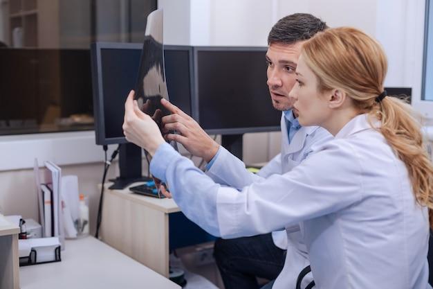 Netter professioneller junger arzt, der das röntgenfoto betrachtet und während der arbeit bespricht