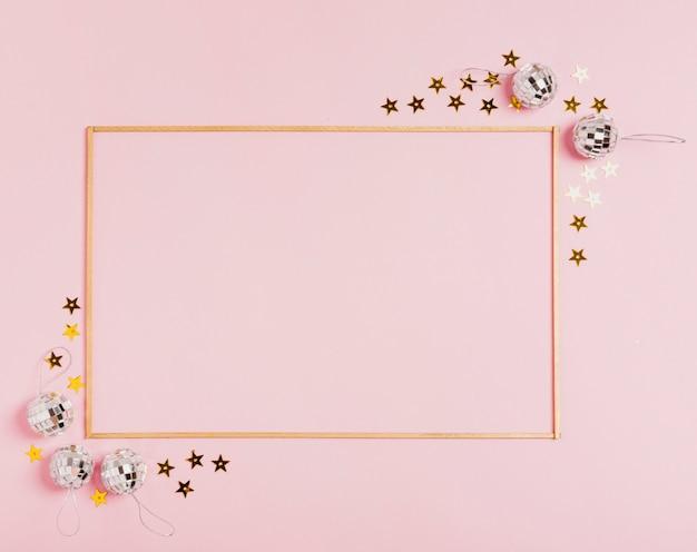 Netter rahmen mit weihnachtsbällen auf rosa hintergrund