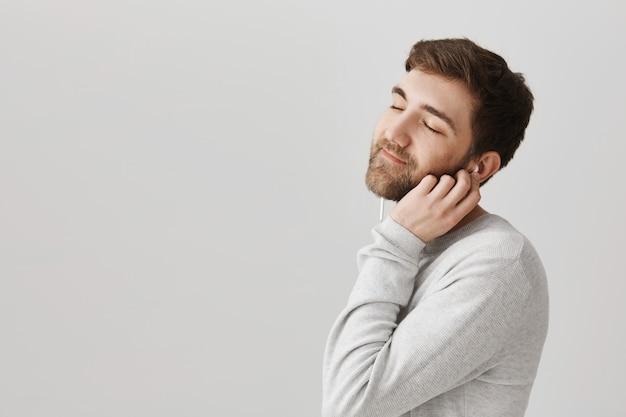 Netter romantischer kerl, der musik in kopfhörern genießt