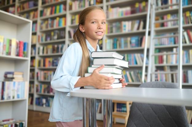 Netter ruhiger schüler, der einen stapel lehrbücher auf den schreibtisch einer öffentlichen bibliothek legt
