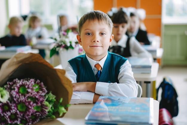 Netter russischer junge, der am 1. september in einem klassenzimmer der neuen modernen schule am schreibtisch sitzt. foto in hoher qualität