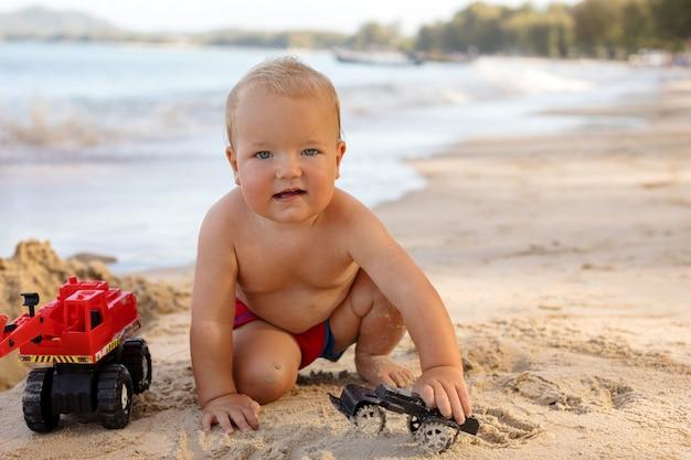 Netter säuglingsjunge, der auf sandigem strand spielt