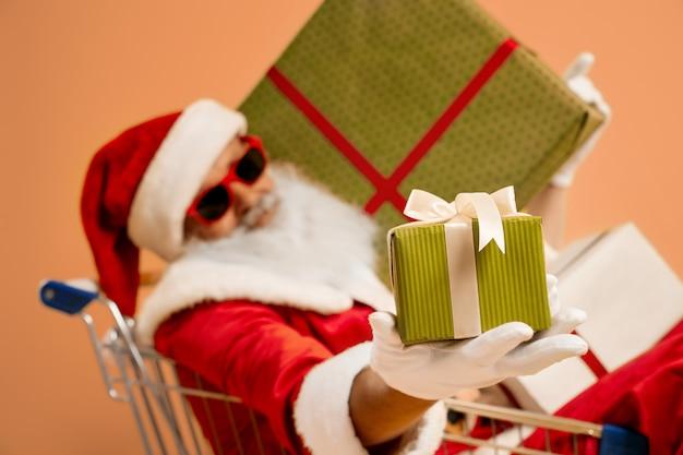 Netter sankt nikolaus im einkaufswagen mit geschenkboxen