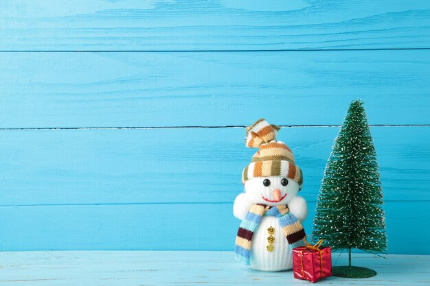 Netter schneemann und geschenk mit weihnachtsbaum auf blauem hölzernem hintergrund