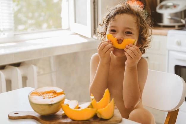 Netter schöner kleiner junge, der frische melone isst.