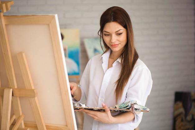 Netter schöner mädchenkünstler, der ein bild auf einer leinwand auf einer staffelei malt. weißer hintergrund des studios. langes haar, brünett. halten sie bunten pinsel und palette.