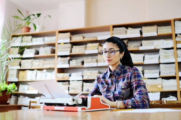 Netter schriftsteller der jungen frau in den gläsern schreibt auf einer schreibmaschine in der hintergrundbibliothek