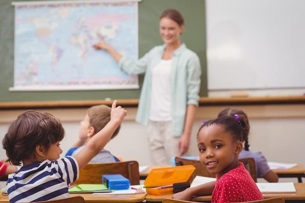 Netter schüler, der an der kamera an seinem schreibtisch im klassenzimmer lächelt
