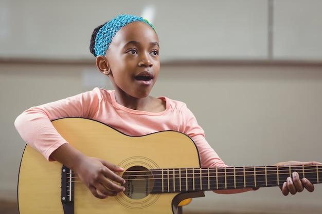 Netter schüler, der gitarre in einem klassenzimmer singt und spielt
