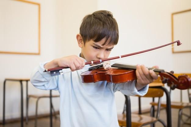 Netter schüler, der violine im klassenzimmer spielt