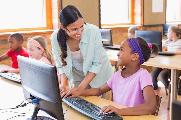 Netter schüler in der computerklasse mit lehrer
