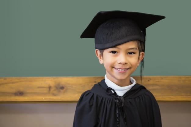 Netter schüler in der staffelungsrobe lächelnd an der kamera im klassenzimmer