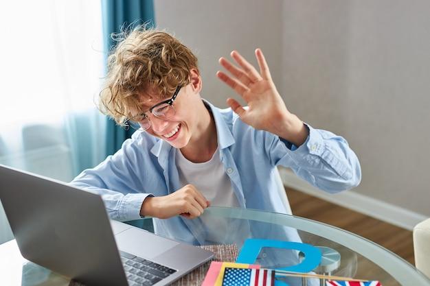 Netter schüler sagt hallo vor der kamera, während er online-unterricht zu hause hat