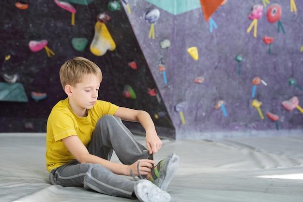 Netter schuljunge in aktivkleidung, der auf dem boden im sportverein sitzt und schnürsenkel auf turnschuh vor dem training bindet
