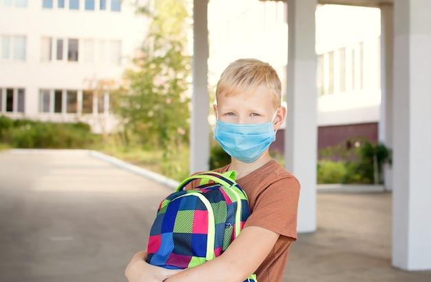Netter schuljunge mit einer schutzmaske und einem rucksack