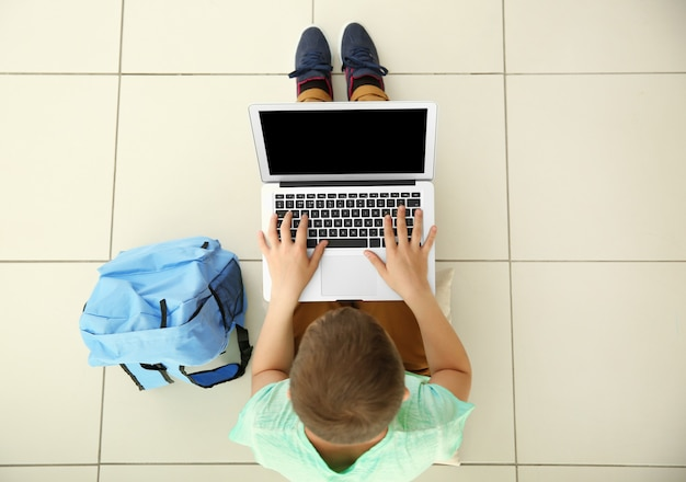 Netter schuljunge mit laptop, draufsicht