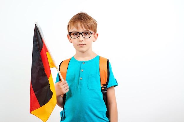 Netter schuljunge mit rucksack, der deutsche flagge, leute, bildung, lernen und schulkonzept hält.