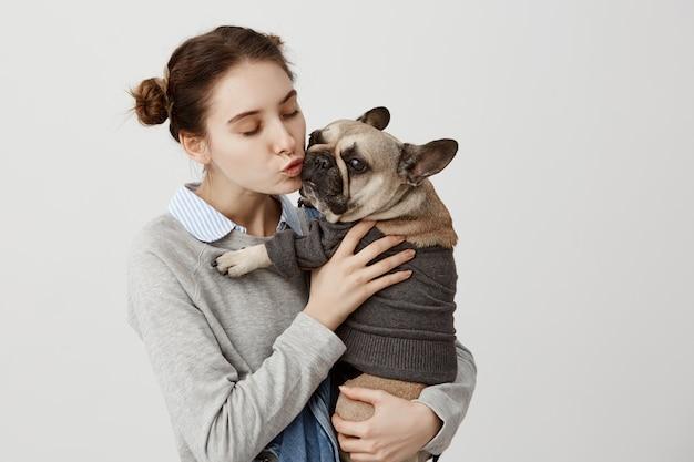 Netter schuss des erwachsenen mädchens, das niedlichen kleinen hund küsst, während es ihn mit zärtlichkeit hält. porträt des hundes und seiner besitzerin, die zeit miteinander kuscheln und freunde sind. anzeige der zuneigung