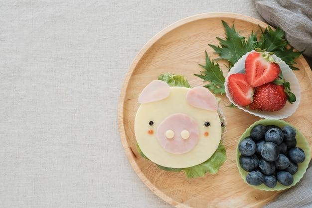 Netter schweinbrot-teller, spaßlebensmittelkunst für kinder, jahr des schweinelebensmittels