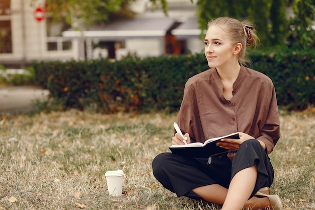 Netter student, der in einem park arbeitet und das notizbuch benutzt