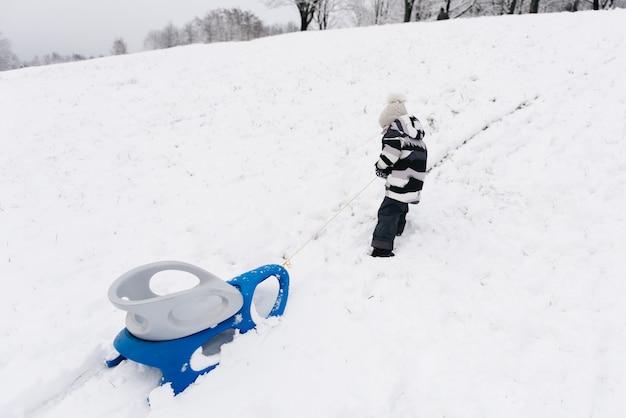 Netter süßer junge in einem schlitten im schnee, aktiver lebensstil, winter, familie