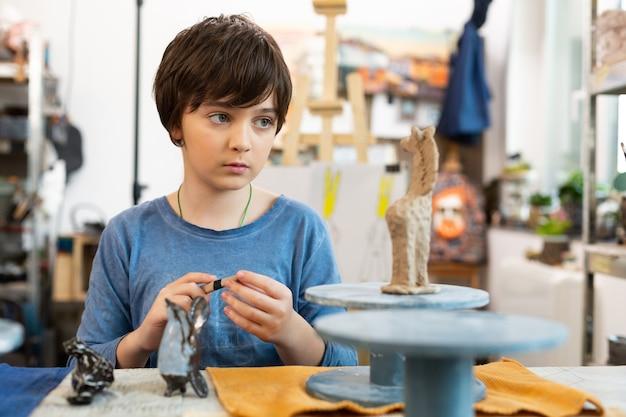 Netter talentierter junge, der kleines tontier in der kunstschule modelliert