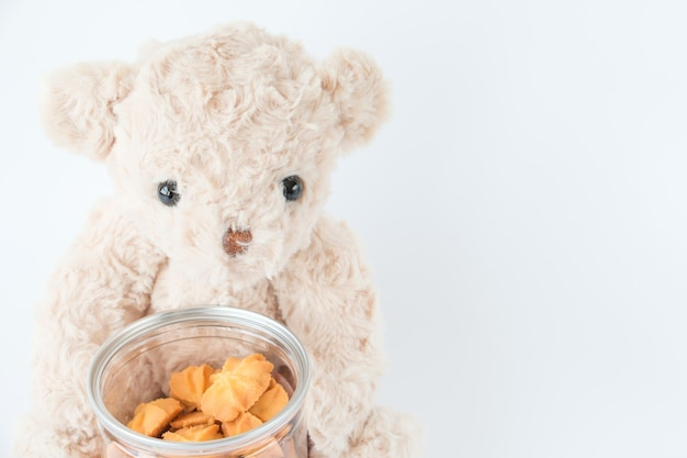 Netter teddybär, der geschmackvollen nachtisch der miniplätzchenvanille hält