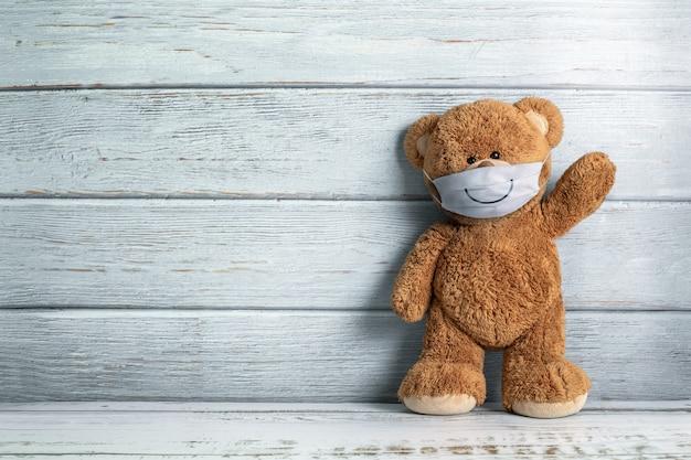 Netter teddybär, der hinter der maske lächelt, hat ein glückliches gesicht für soziales distanzierungskonzept. mit kopierraum.