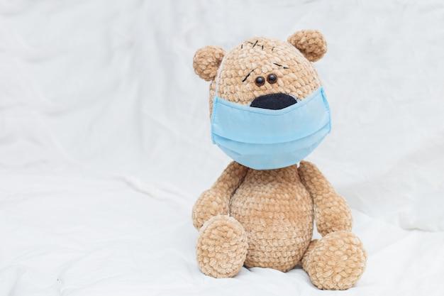 Netter teddybär mit gesichtsmaske auf seinem mund auf bett. quarantänekonzept, schutz vor covid-19-viren.