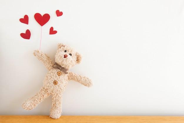 Netter teddybär mit rotem herzen steigt im ballon auf, er glücklich und lächelnd, glückliches valentinstagkonzept.