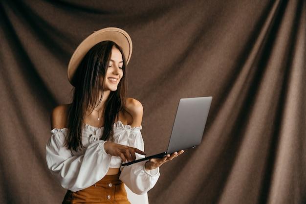 Netter teenager beeindruckt rabatt unglaubliches wunder moderne technologie gadget apps blogger isoliert braunen hintergrund. hochwertiges foto
