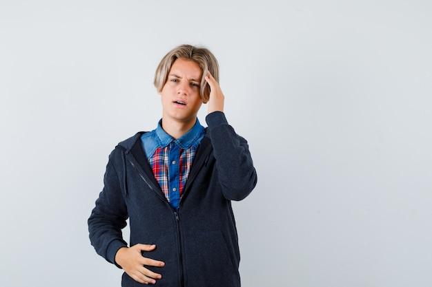 Netter teenager, der die hand im hemd, hoodie und vergesslich auf dem kopf hält. vorderansicht.