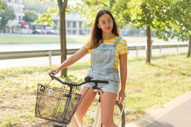 Netter teenager, der fahrrad draußen reitet