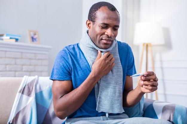 Netter trauriger junger mann, der schal trägt und das thermometer betrachtet, während er eine körpertemperatur hat