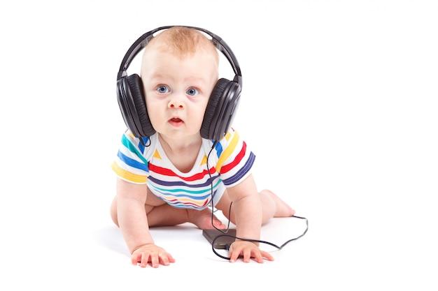 Netter überraschter kleiner junge im bunten hemd mit kopfhörern auf kopf