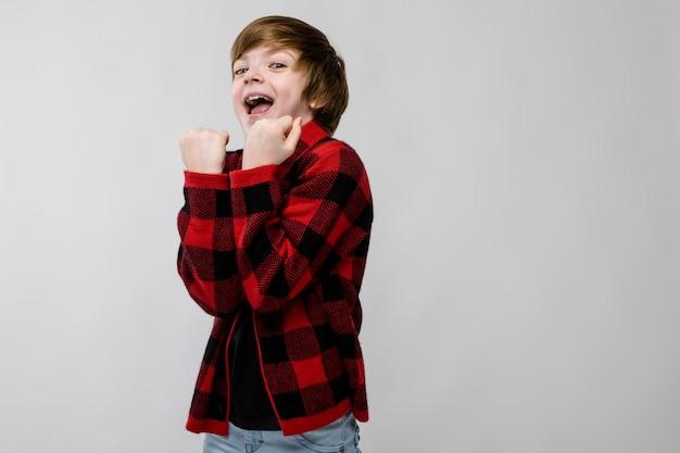 Netter überzeugter aufgeregter lächelnder kleiner kaukasischer junge im karierten hemd, das ja zeichen auf grau zeigt