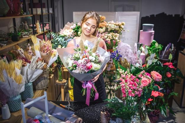 Netter und attraktiver florist gehört zu den bunten blumen. sie hält die bouqette in den händen und schaut sie sich an. junge frau lächelt.