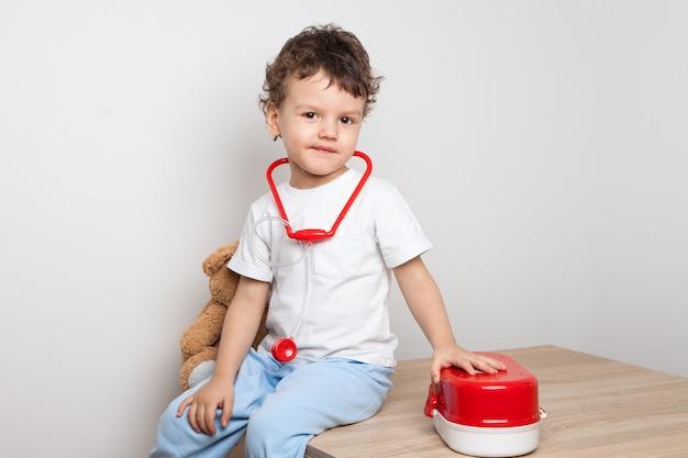 Netter und lustiger lockiger junge, der auf einem tisch mit einem erste-hilfe-satz und einem stethoskop an seinem hals sitzt. ein spiel des doktors. babyaktivitäten zu hause. gewöhnung an medizinische verfahren. spiel im beruf