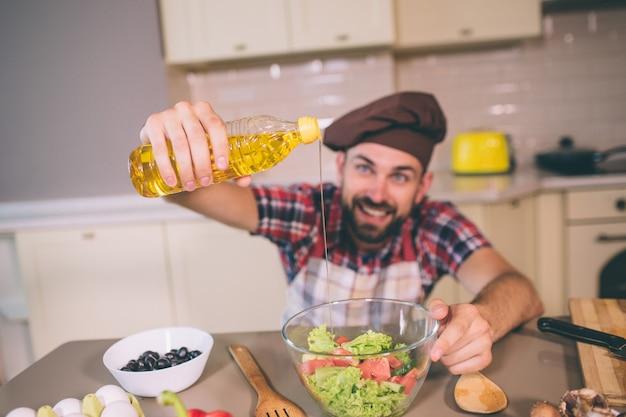 Netter und positiver chef steht in der küche am tisch und hält eine flasche öl. er gießt etwas davon in eine schüssel mit salat. er sieht glücklich und aufgeregt aus.