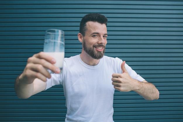 Netter und positiver mann hält ein glas mils und zeigt großen daumen hoch. er mag es. guy schaut vor die kamera und lächelt. isoliert auf gestreift