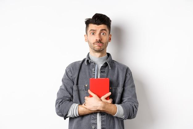 Netter und schüchterner kerl, der sein tagebuch umarmt, rotes tagebuch hält und bescheiden in die kamera schaut, vor weißem hintergrund stehend.