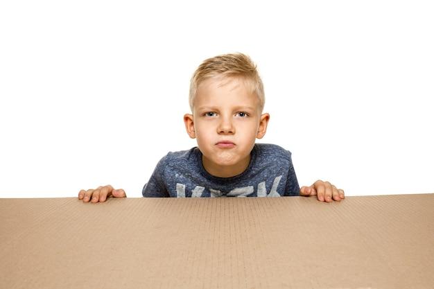 Netter und verärgerter kleiner junge, der das größte paket öffnet. enttäuschtes junges männliches model auf karton cardboard