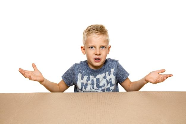Netter und verärgerter kleiner junge, der das größte postpaket öffnet. enttäuschtes junges männliches model auf karton cardboard