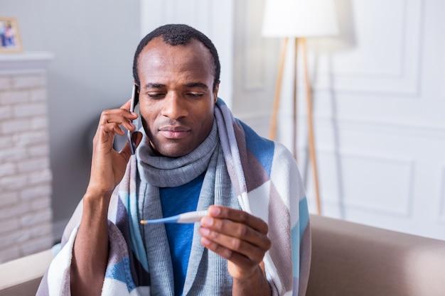 Netter unglücklicher freudloser mann, der ein thermometer durchlöchert und anruft, während er zu seinem arzt ruft
