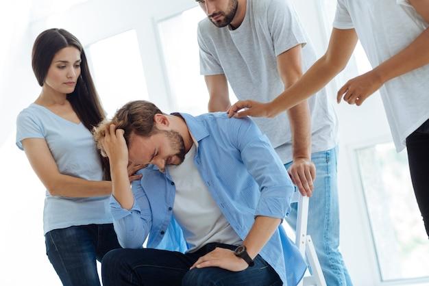 Netter unglücklicher freudloser mann, der seine haare hält und über persönliche probleme nachdenkt, während er eine chronische depression hat