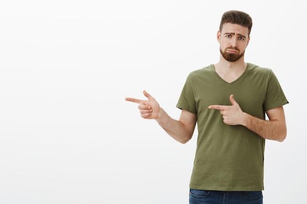 Netter unglücklicher und verärgerter mann, der schmollt und die stirn runzelt wie düsterer welpe, als er nach links zeigt, enttäuscht
