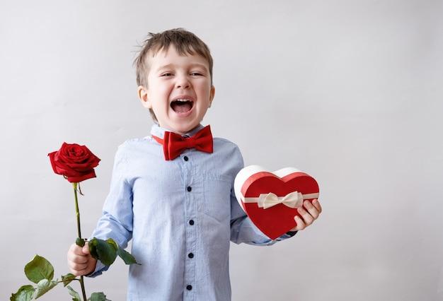 Netter verlassener kleiner kaukasischer junge in fliege mit geschenkbox des roten herzens und rose. valentinstag.